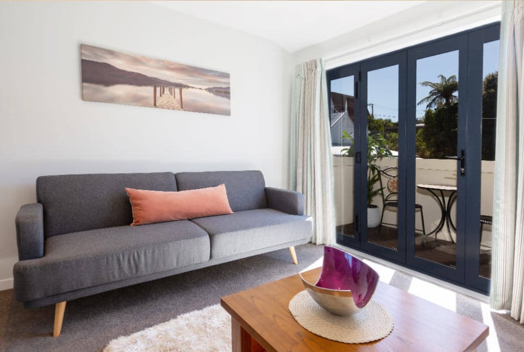 Open plan living leading out onto sunny deck or courtyard in the two bedroom Huntleigh Apartments.