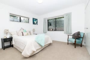 Spacious bedroom with an abundance of natural light and large wardrobes in the two bedroom villas on Edith Collier Drive.
